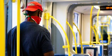 Man with face mask inside a train alone